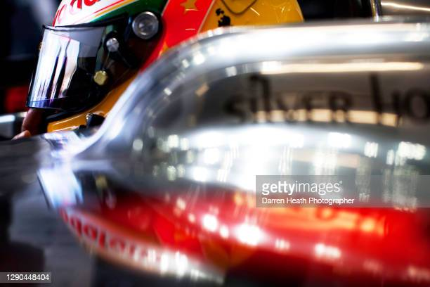 British McLaren Formula One racing driver Lewis Hamilton driving sitting in his McLaren MP4-25 racing car in the team's pit garage during practice...