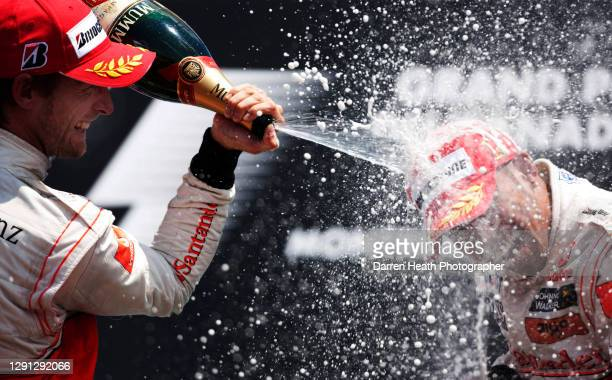 British McLaren Formula One racing driver Lewis Hamilton with his McLaren teammate Jenson Button celebrating by spraying champagne on the winners...