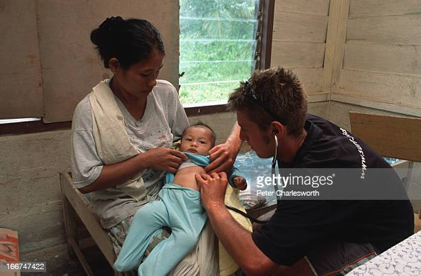 British Medical student Oliver Jenkins checks on the health of a baby called Jardi held by his mother Mariani Mardi in a tiny clinic on Siberut...