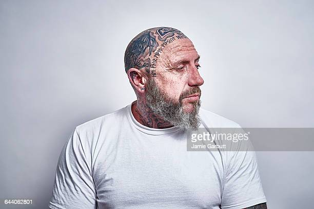 British middle aged male with tattooed head