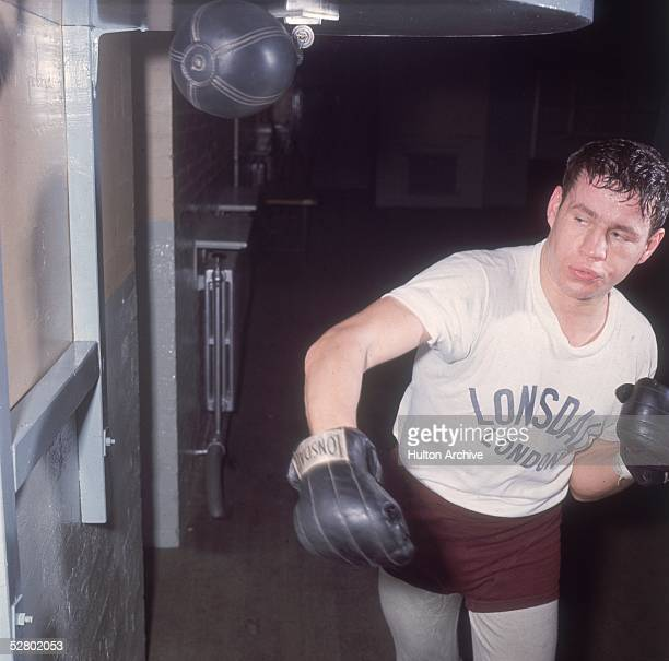 British middleweight boxer Terry Downes training with a punch bag at the gym 1962