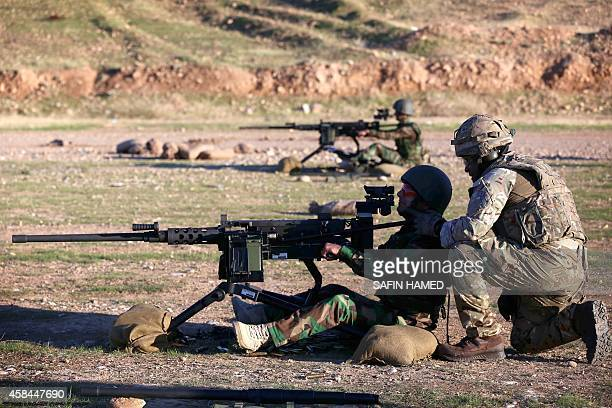 British military advisers instruct Kurdish Peshmerga fighters during a training session at a shooting range on the outskirts of Arbil the capital of...