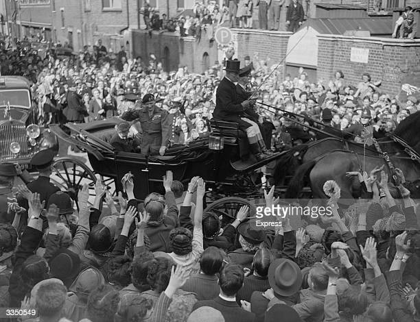 British military leader Field Marshal Bernard L. Montgomery, Viscount Montgomery of Alamein, waving as his carriage passes through crowds in the...