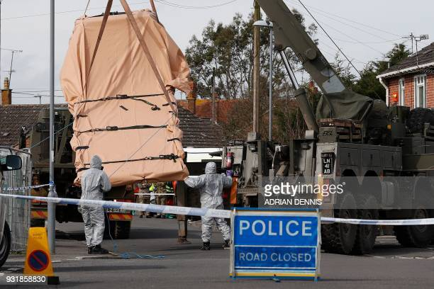 British Military personnel wearing protective coveralls work to remove a vehicle connected to the March 4 nerve agent attack in Salisbury, from a...