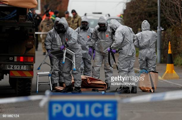 British Military personnel wearing protective coveralls work to remove a vehicle connected to the March 4 nerve agent attack in Salisbury from a...