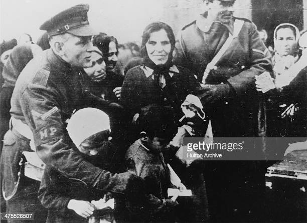 British military police officers guide children through a crowd of Greek civilians to receive rations from a British military-run food kitchen in...