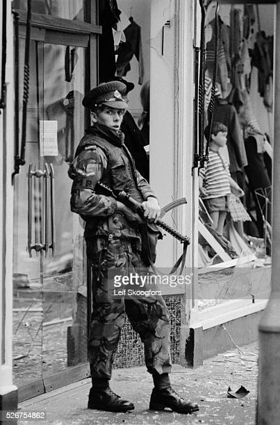 A British Military Police soldier holds a L2A3 9mm submachine gun on the scene of an Irish Republican Army bombing Belfast Northern Ireland