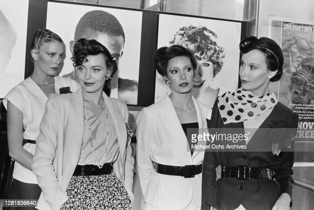 British model and actress Lesley-Anne Down with three other models wearing 70s hairstyles, 28th March 1979. On the right is a poster for the film...