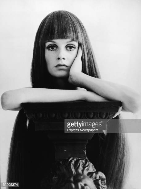 British model and actress Twiggy holds her head in her hand and leans on a pedestal while she wears a long dark wig, late 1960s.