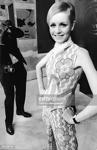 British model and actress Twiggy stands with arms akimbo and wears a psychadelic pants suit which is part of her clothing line while a photographer...