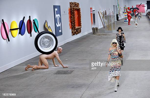 British model Cara Delevingne presents a creation for Chanel during the 2014 Spring/Summer readytowear collection fashion show on October 1 2013 at...