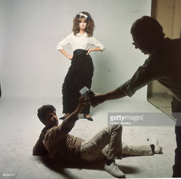 British model Jean Shrimpton poses for a shoot while American photographer Richard Avedon lays on the floor taking a camera from an assistant...