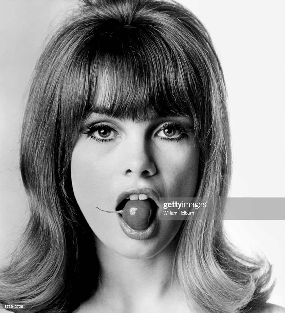 British model Jean Shrimpton posing with a radish in her mouth, 1964.