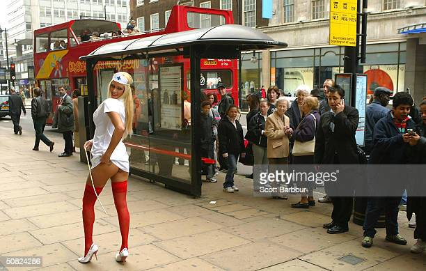 British model Luci Victoria poses for photographers as pedestrians watch May 11 2004 in London England Victoria wore a nurses outfit to mark National...