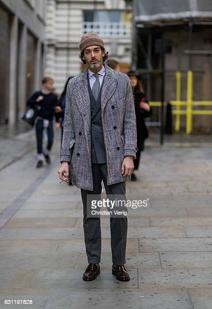 British model Richard Biedul wearing a grey wool coat grey suit beanie during London Fashion Week Men's January 2017 collections at Lou Dalton on...