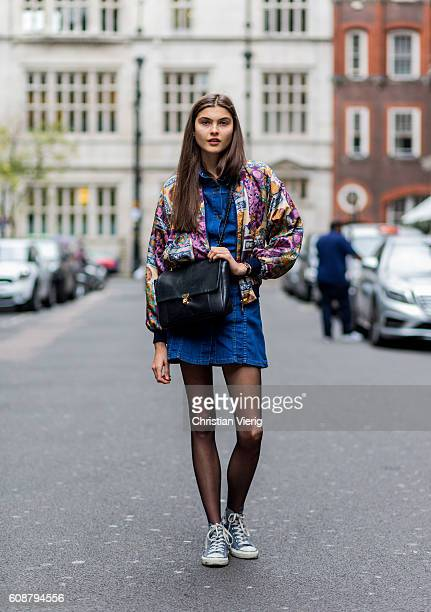 British model Thea Hudson wearing a denim dress Converse shoes and bomber jacket with floral print outside Christopher Kane during London Fashion...