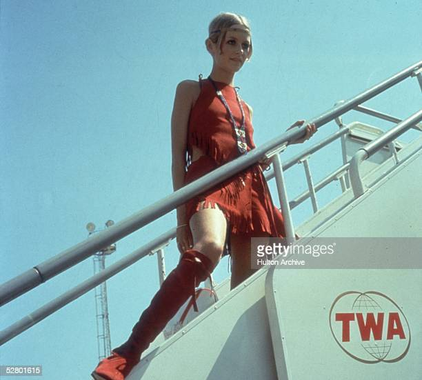 British model Twiggy boarding a TWA plane at Heathrow Airport mid 1960s She is wearing a red tasselled native American style outfit and matching boots