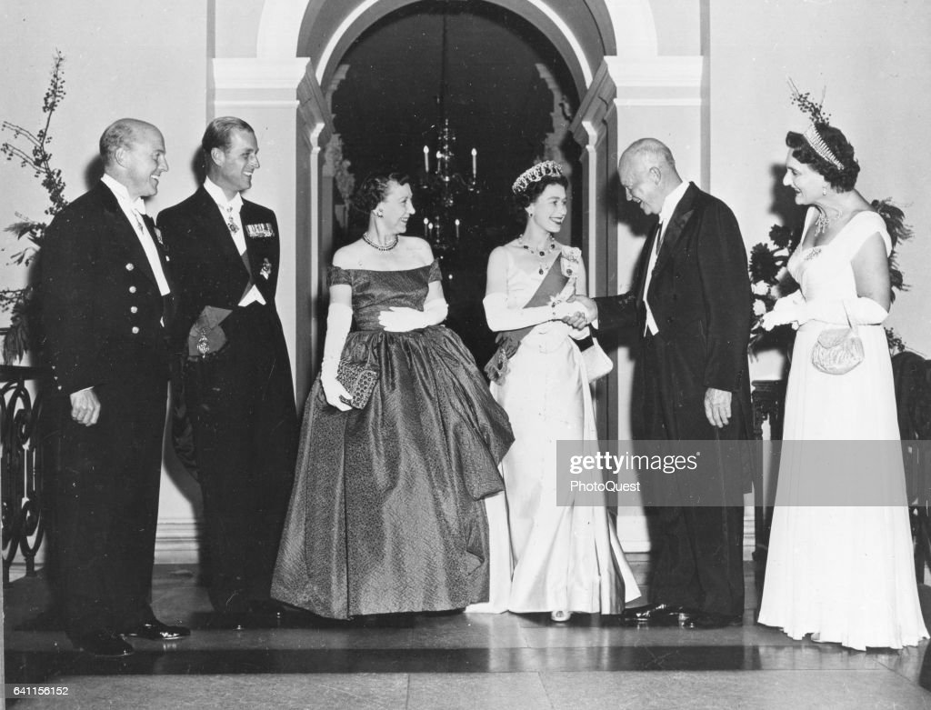 British monarch Queen Elizabeth (third right) shakes hands with US President Dwight D Eisenhower at the White House during a state visit, Washington DC, 1957. Also pictured are, British Ambassador to the US Baron Harold Caccia, Prince Philip of Great Britain, Mamie Eisenhower, and Lady Anne Caccia.