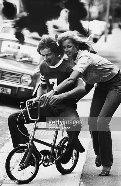 British motorbike champion Barry Sheene tries his hand at a small Chipper bicycle with the aid of his future wife glamour model Stephanie McLean July...