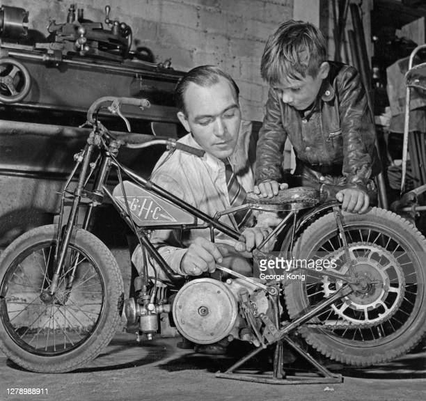British motorcycle builder Howard Cole and his son, British motorcycle speedway rider Howard Cole , aged six, wearing a leather jacket, inspect a...