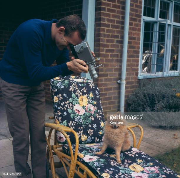 British motorcycle racer Mike Hailwood filming a small dog, circa 1970.