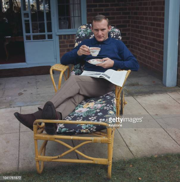 British motorcycle racer Mike Hailwood relaxing with a cup of tea, circa 1970.