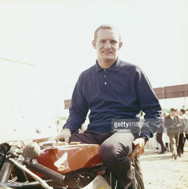 British motorcycle road racer Mike Hailwood pictured seated on a Honda RC162 250cc motorbike at a racetrack in September 1961. Mike Hailwood would go...