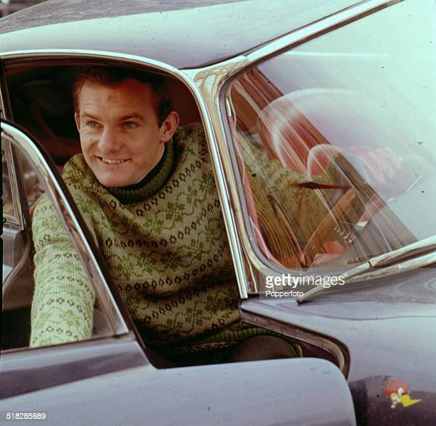 British motorcycle road racer Mike Hailwood posed sitting in the driver's seat of a car wearing a knitted Fair Isle jumper in 1965.