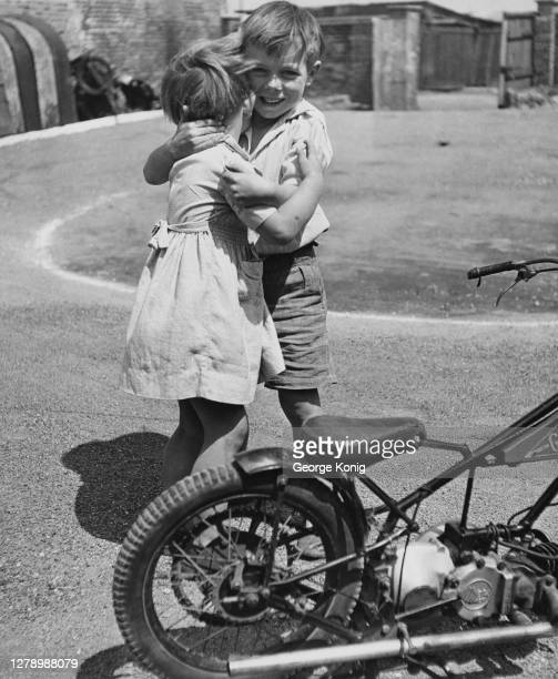 British motorcycle speedway rider Howard Cole , aged six, hugging his four-year-old sister, Janet, beside his scaled-down speedway bike in...