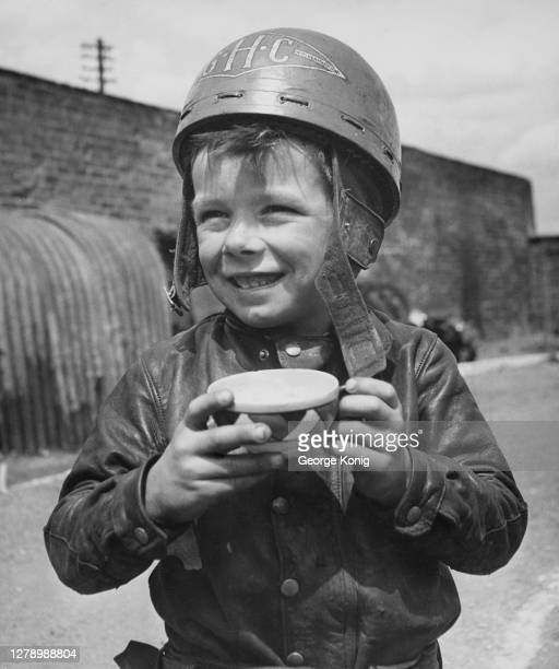 British motorcycle speedway rider Howard Cole , aged six, wearing a leather jacket and holding a cup of tea, his helmet bearing his initials 'GHC' ,...