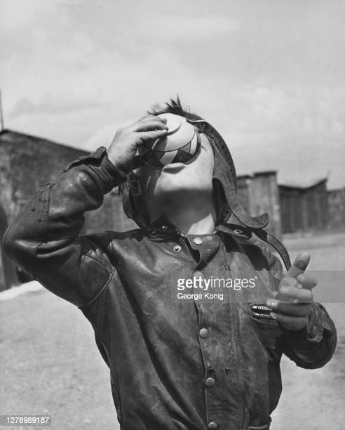 British motorcycle speedway rider Howard Cole aged six wearing a leather jacket tips his head back to drink a cup of tea at his private speedway...