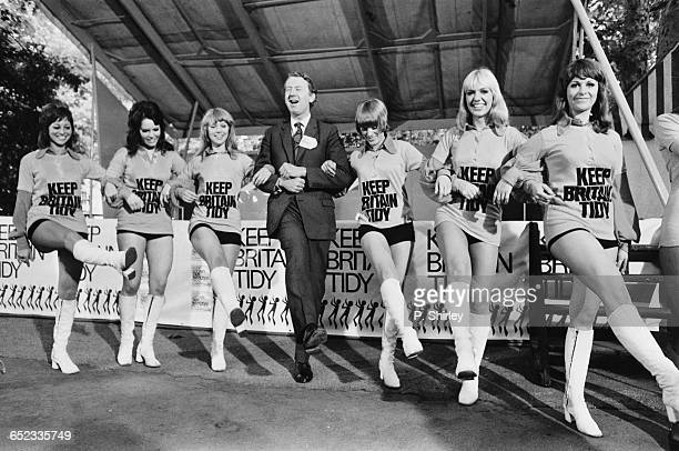British MP Peter Walker Baron Walker of Worcester links arms with a group of dancers during the 'Keep Britain Tidy' campaign London UK 5th July 1971