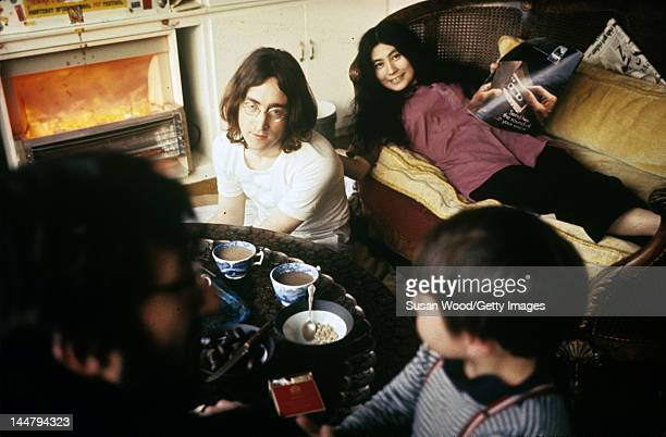 British musican and artist John Lennon and Japanese-born artist and musician Yoko Ono watch an unidentified man and child , December 1968.