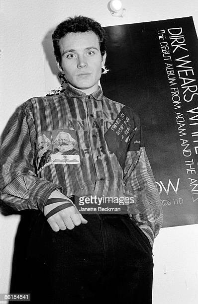 British musician Adam Ant poses in the office of Do It Records in front of a poster advertising the record 'Dirk Wears White Sox' the debut album by...
