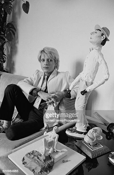 British musician and bass player with the group Japan Mick Karn pictured sitting on a sofa with various artworks in London on 12th June 1980
