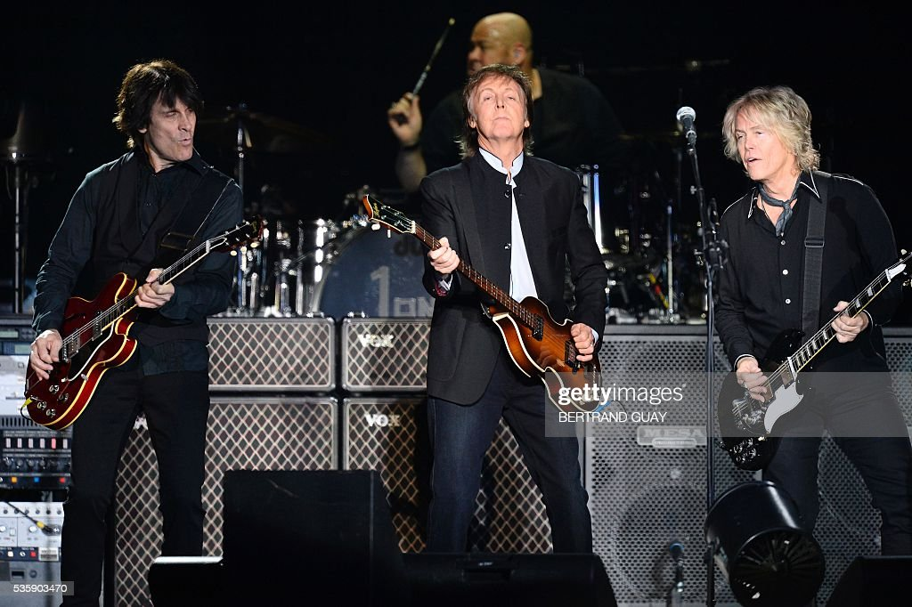 British musician and former Beatles' member Paul McCartney (C) performs on stage at the Bercy stadium in Paris on May 30, 2016. / AFP / BERTRAND