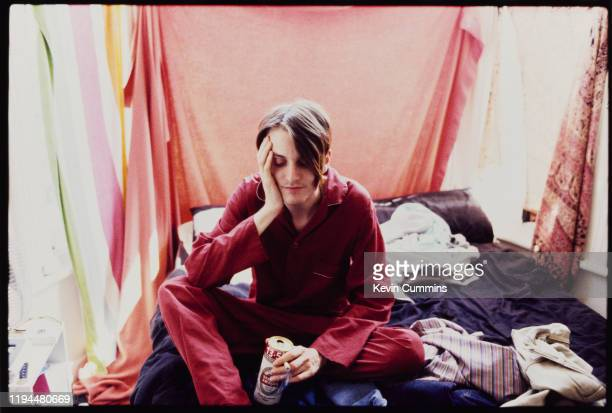 British musician and singer Johnny Dean of Britpop band Menswear holds a can of Stella Artois beer as he smokes a cigarette on a bed, UK, circa 1995.