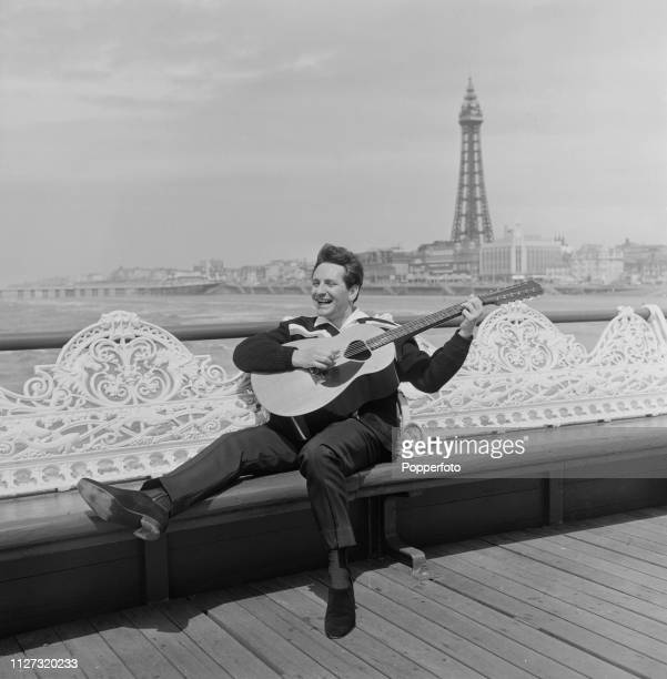 British musician and singer Lonnie Donegan pictured playing a 12 string acoustic guitar on the South Pier in Blackpool, England in July 1963.