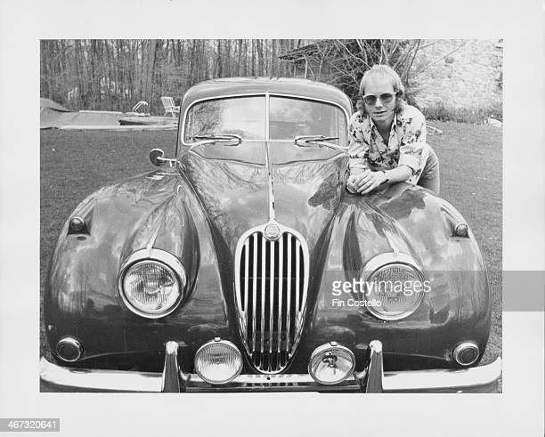 British musician Andy Powell of the band Wishbone Ash posing with his Jaguar circa 1975