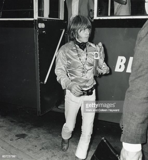 British musician Brian Jones of the group the Rolling Stones carries a newspaper as he steps off a bus at an unidentified airport July 28 1967