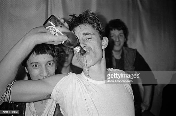 British musician Jimmy Pursey of the group Sham 69 drinks a Heineken backstage at the Mudd Club after a performance New York New York December 4 1979