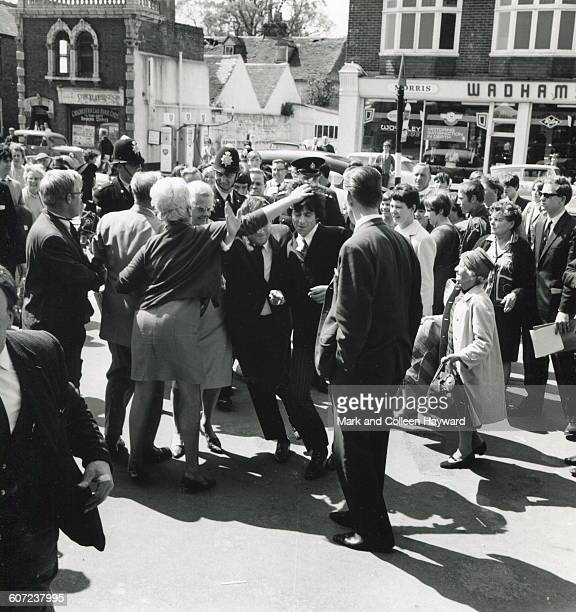 British musician Keith Richards of the Rolling Stones is escorted through a crowd near Chichester Magistrates Court Chichester England May 27 1967...