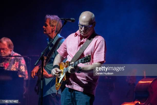 British musician Mark Knopfler OBE plays guitar as he performs on stage at Arena Leipzig Leipzig Germany July 5 2019 Visible behind him are band...