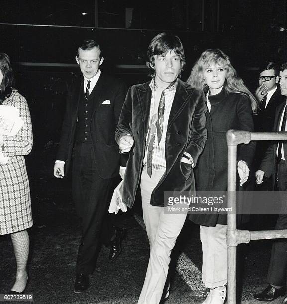 British musician Mick Jagger of the group the Rolling Stones and musician actress Marianne Faithfull walk together at an unidentified airport March...