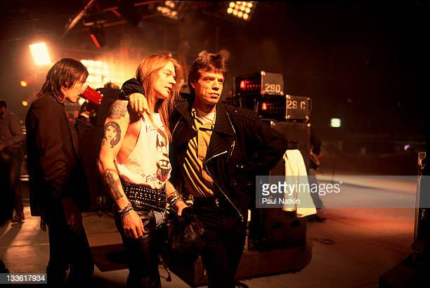 British musician Mick Jagger of the Rolling Stones poses on stage with American musician Axl Rose during the band's 'Steel Wheels' tour late 1989...