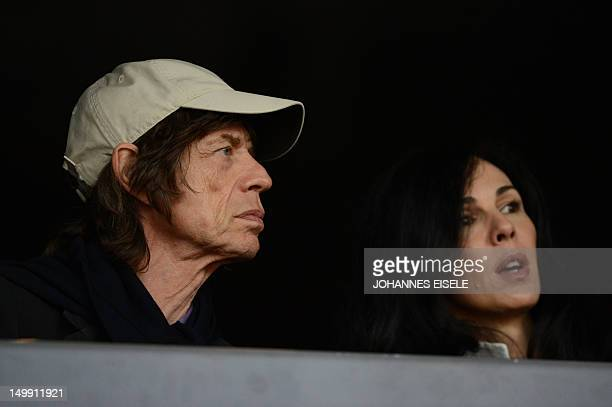 British musician Mick Jagger's and his partner US fashion designer L'wren scott attend the athletics event held at the Olympic Stadium during the...