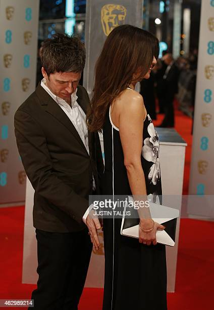 British musician Noel Gallagher and his wife Sara pose for pictures as they arrive on the red carpet for the BAFTA British Academy Film Awards at the...