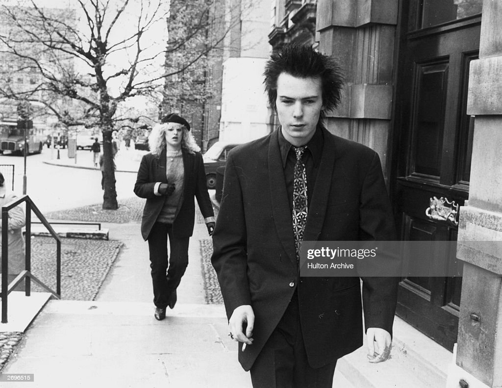 British musician Sid Vicious, bass player and vocalist for the British punk rock band The Sex Pistols, smokes a cigarette while walking up a flight of stairs in front of his girlfriend, Nancy Spungen, on a street in London, England. Vicious has dark spiky hair and wears a dark suit with a dark shirt and tie.