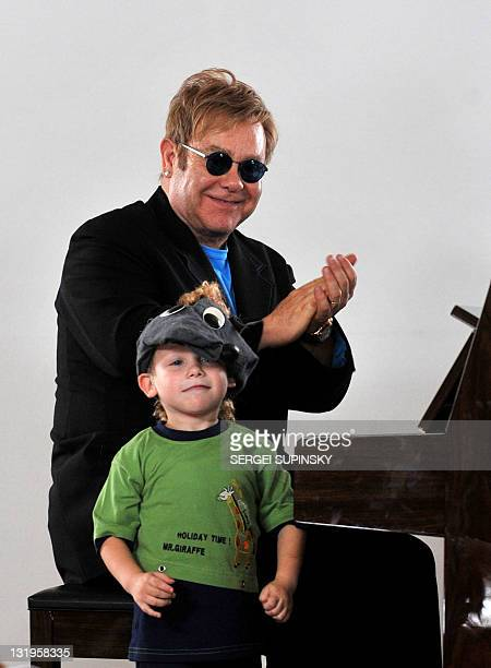 British musician Sir Elton John applauds a young patients at a specialized orphanage for HIVpositive children after the first results of the Children...
