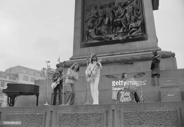 British musicians and brothers Maurice Gibb Robin Gibb and Barry Gibb of pop group Bee Gees performing and filming at foot of Nelson's Column...